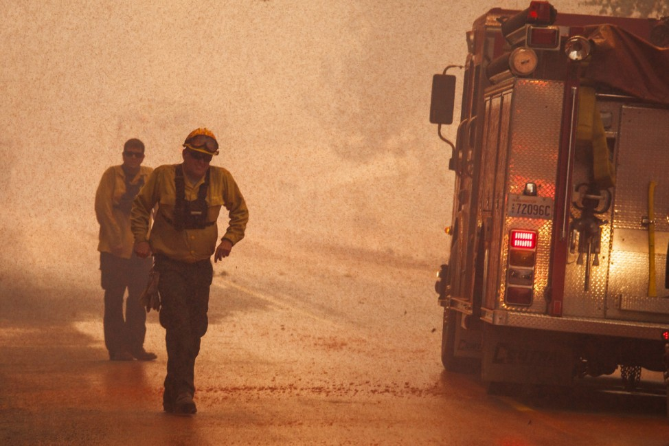 Firefighters are doused with flame retardant from an airplane while fighting the Twisp River fire near Twisp, Washington