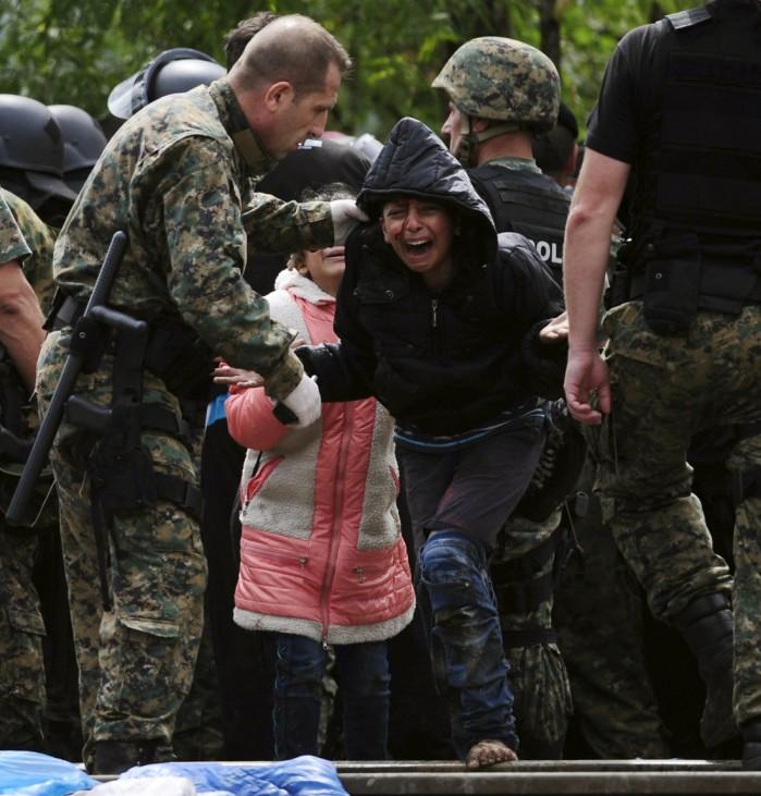 A girl cries after crossing Greece's border into Macedonia near Gevgelija, Macedonia
