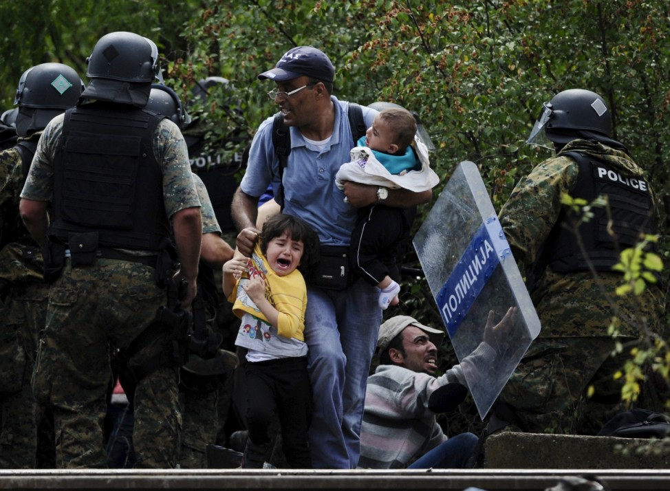 A man holds two children after crossing Greece's border into Macedonia near Gevgelija, Macedonia