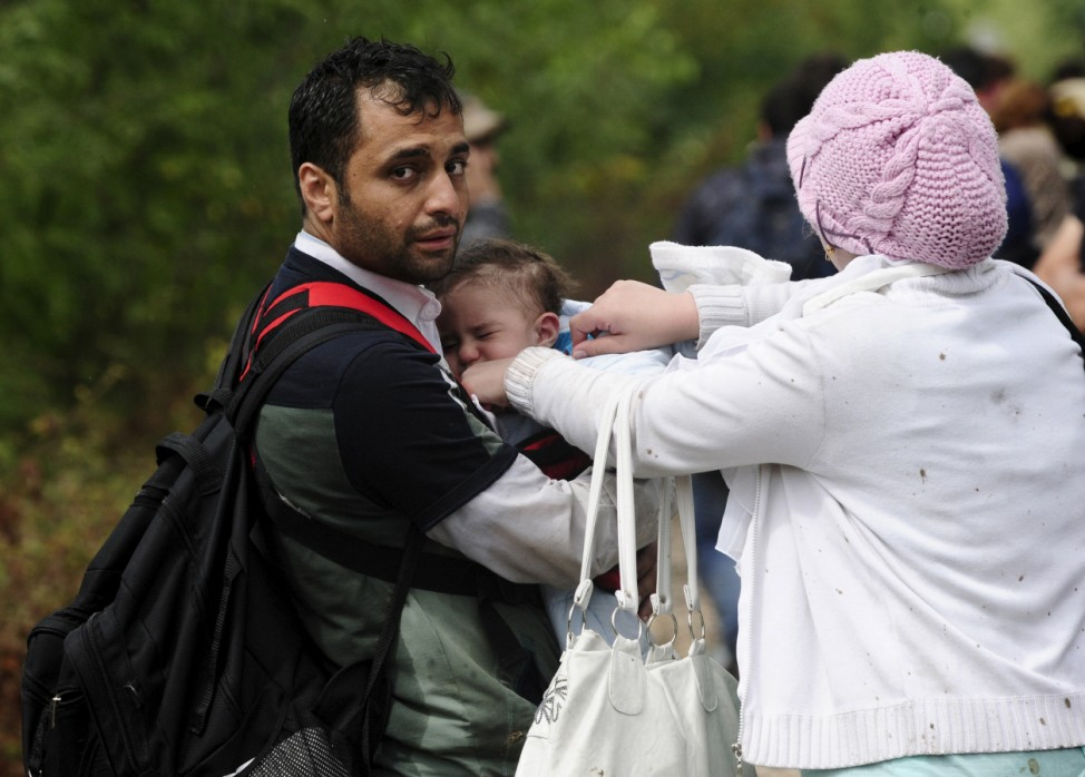 A migrant holds a baby before walking towards Gevgelija in Macedonia after crossing Greece's border