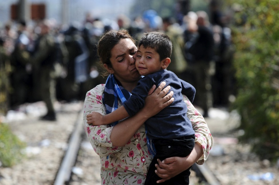 A woman carries a boy after crossing Greece's border into Macedonia near Gevgelija, Macedonia