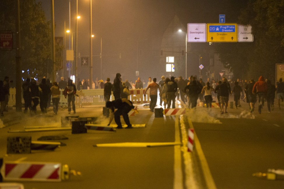Right wing protesters who are against bringing asylum seekers to an accomodation facility run down a street in Heidenau