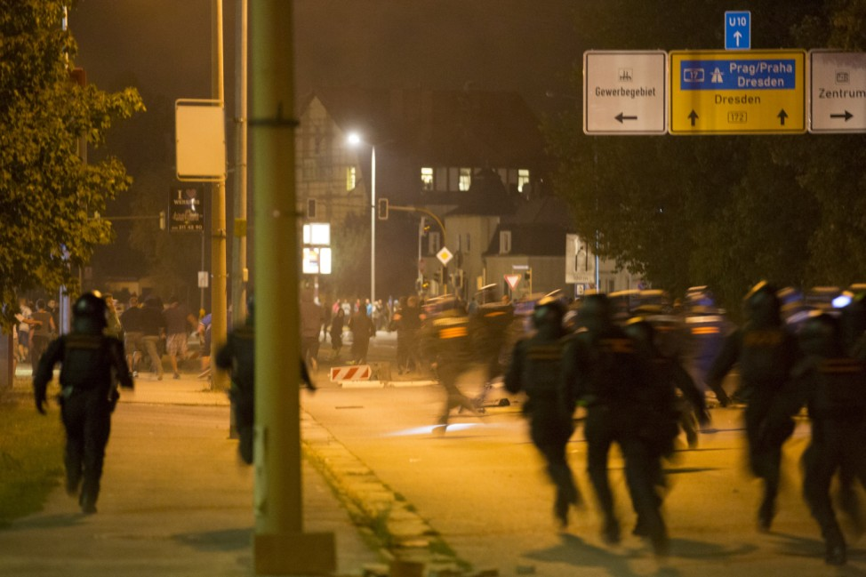 Policemen run after right wing protesters who are against bringing asylum seekers to an accomodation facility in Heidenau