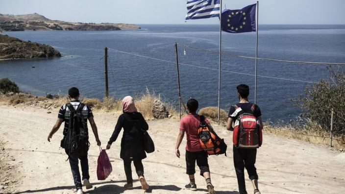 Flüchtlingspolitik: Flüchtlinge aus Syrien passieren die griechische und die europäische Flagge.