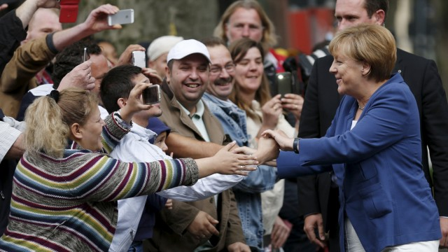 German Chancellor Merkel shakes hands with people before a forum discussion organized by the Chancellery in Duisburg