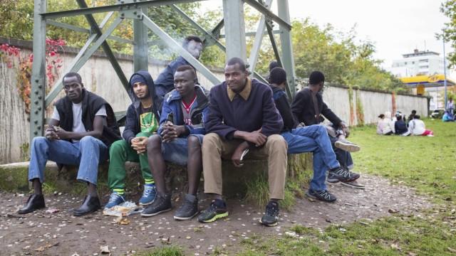 Flüchtlinge sitzen am 15 10 2014 vor der Bayernkaserne in München Die steigenden Flüchtlingszahlen