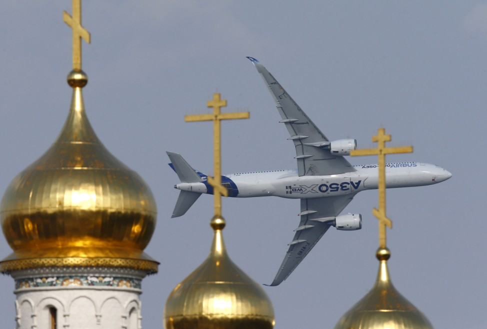Airbus A350 XWB aircraft flies over the domes of an Orthodox church during the MAKS International Aviation and Space Salon in Zhukovsky, outside Moscow, Russia