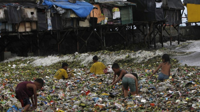 Children sift through floating garbage as they collect recyclable items to sell while strong waves crash along the shores of Manila Bay, near a slum area in Manila