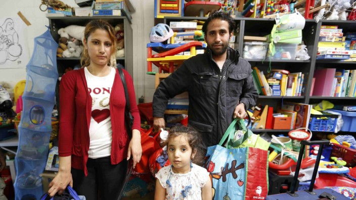 Refugee Lilas, 4, from Syria and her parents receive articles for daily use prepared by donors at a distribution centre in Muelheim an der Ruhr