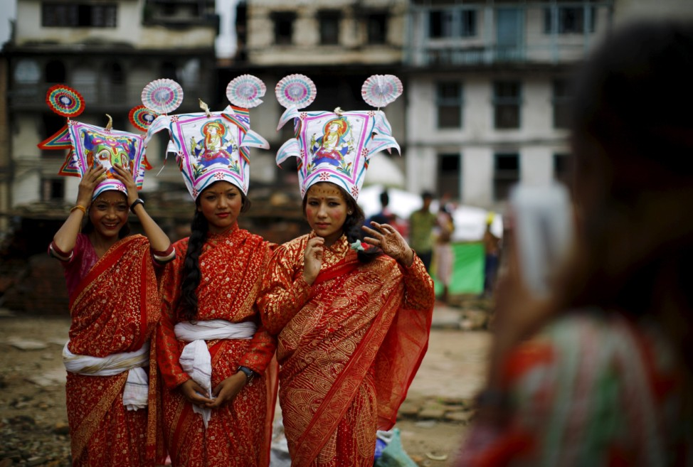 Girls depicting holy cows pose for pictures for a friend before they take part in a parade to mark the Gaijatra Festival in Kathmandu