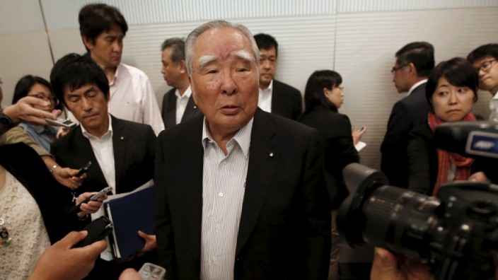 Suzuki Motor Chairman and CEO Osamu Suzuki is surrounded by media at a news conference in Tokyo