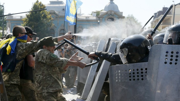 Demonstrators, who are against a constitutional amendment on decentralization, clash with police outside the parliament building in Kiev