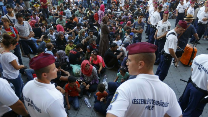 Hungarian police officers watch migrants outside the main Eastern Railway station in Budapest
