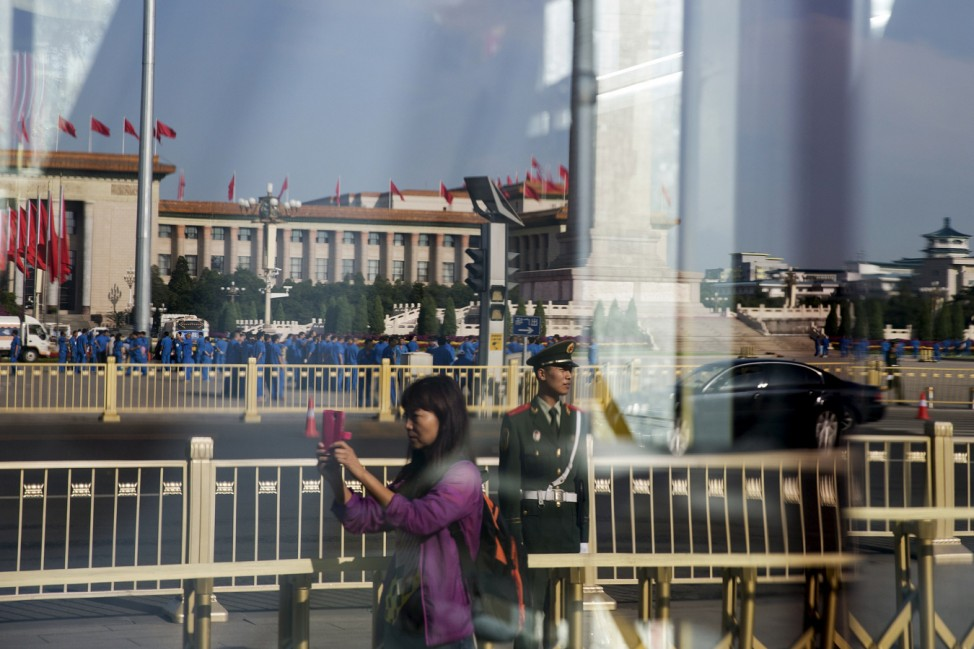 A woman takes pictures at Beijing's Tiananmen Square as the capital prepares for tomorrow's parade