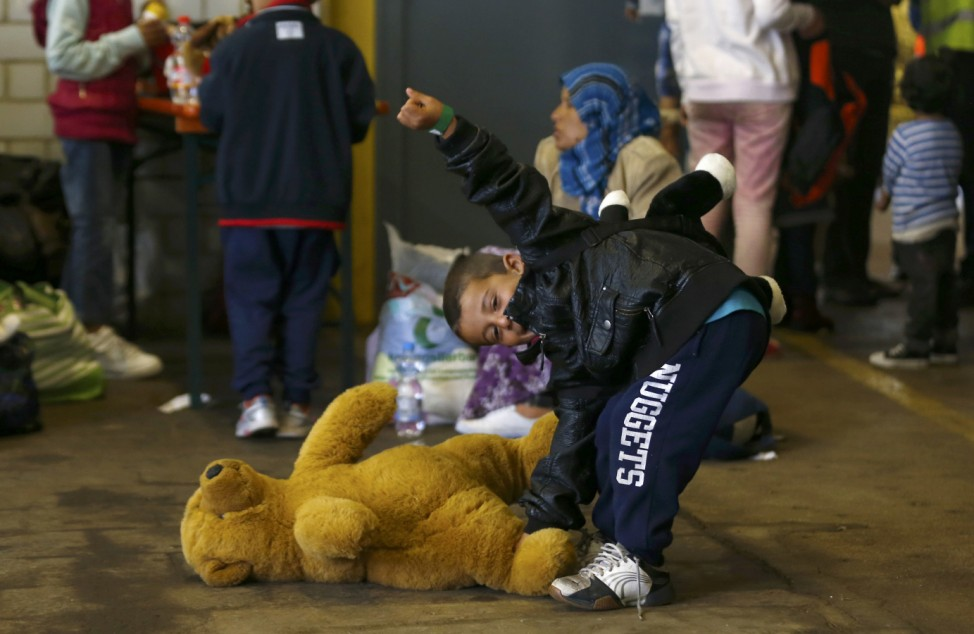 A young boy smiles after receiving a teddy bear at the registration point for migrant arrivals at the main station in Munich