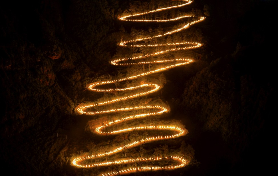 People holding torches walk on a mountain trail during a trekking event to mark the 70th anniversary of the end of World War Two, in Qinglong county