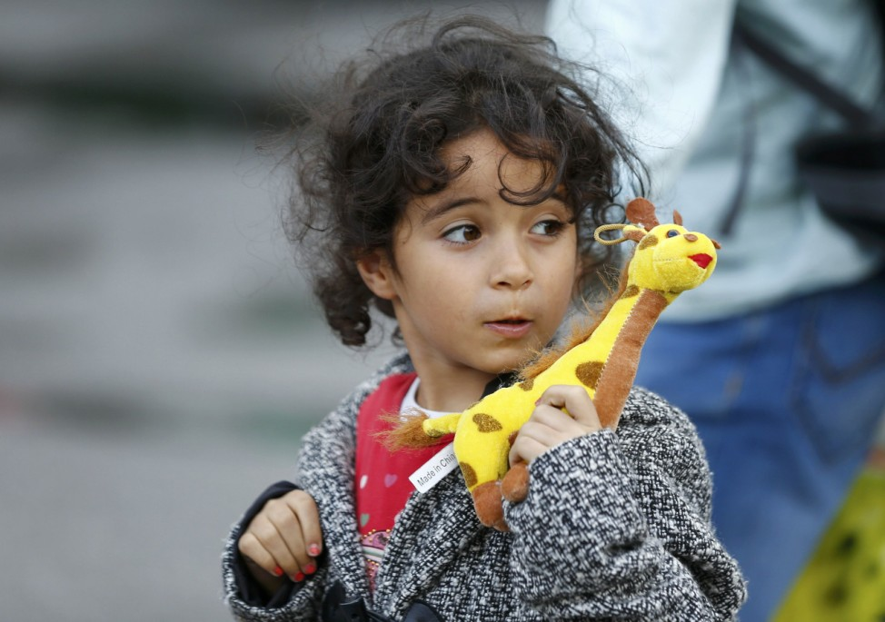 A migrant child walks after arriving by train to the main railway station in Munich