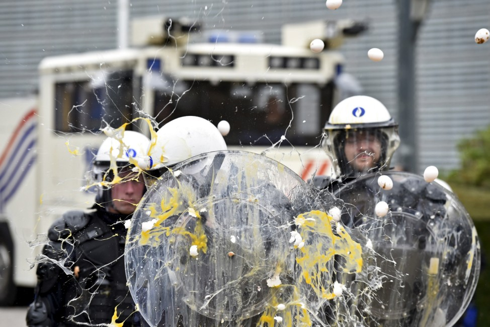 Policemen are hit by eggs as farmers and dairy farmers from all over Europe take part in a demonstration in Brussels