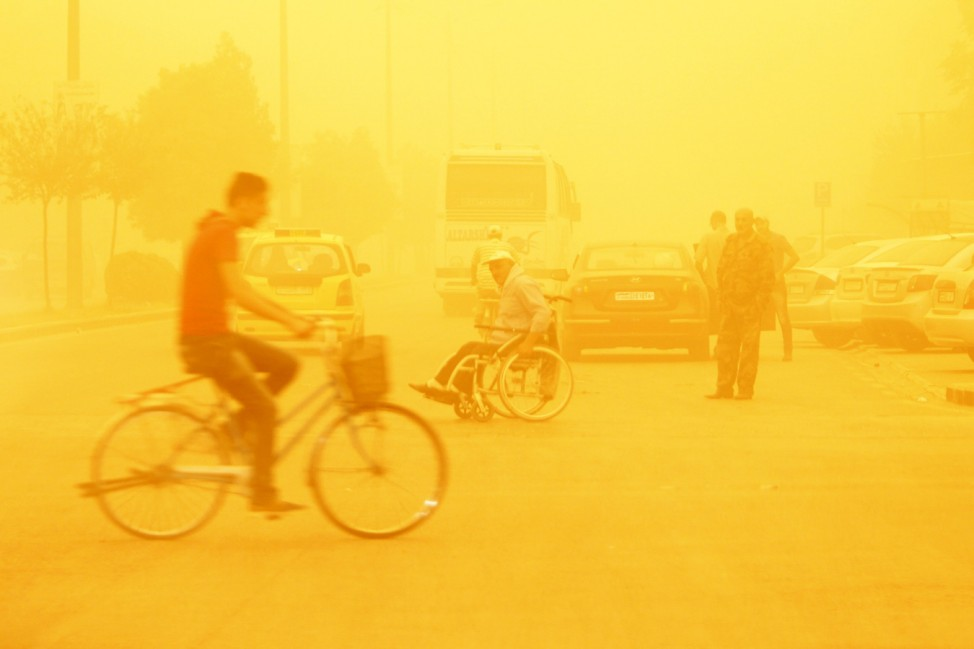 A man rides a bicycle through a sandstorm in Homs