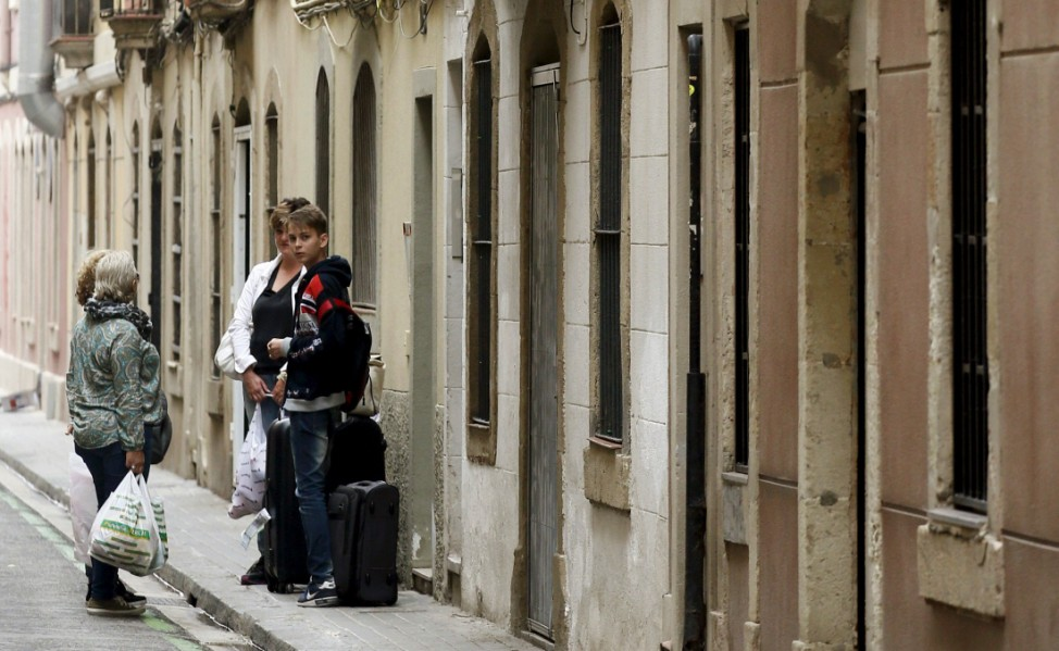 Tourists wait at an apartment door as a woman looks on from a balcony at Barceloneta neighborhood in Barcelona