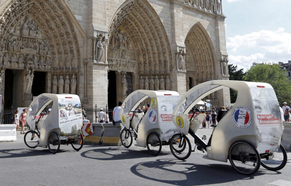 Tricycles for tourists are parked in front of the Notre Dame Cathedral in Paris