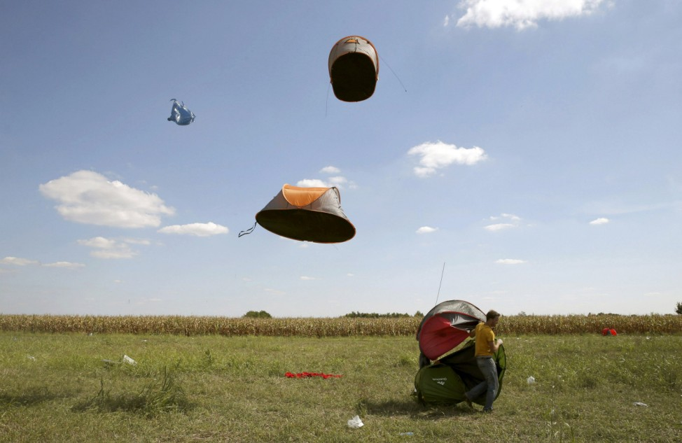 Migrants' tents are blown off by the wind near a collection point in the village of Roszke