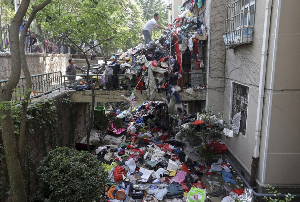 A pile of garbage is seen blocking an entrance to a residential building as workers clean up one of its apartments, in Qingdao