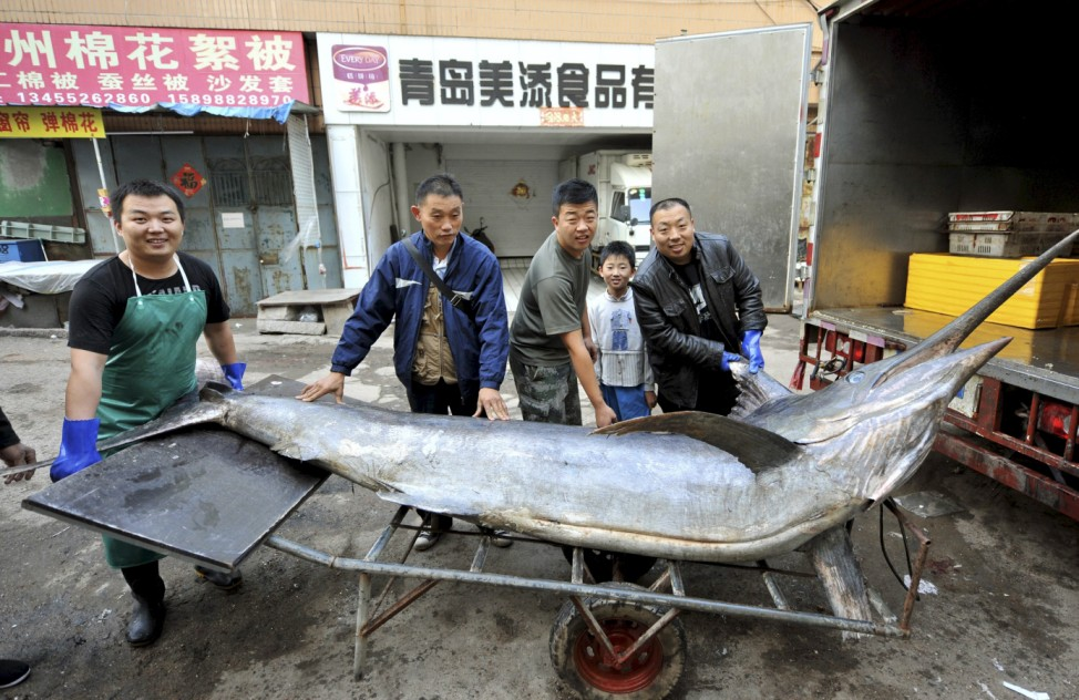 Seafood vendors pose for photographs with a giant swordfish after unloading it from a truck, in Qingdao