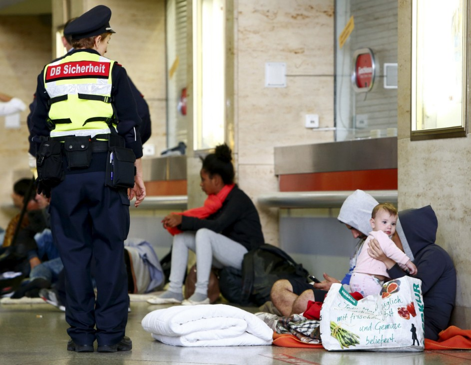 Migrants wait in hall of the main railway station in Munich