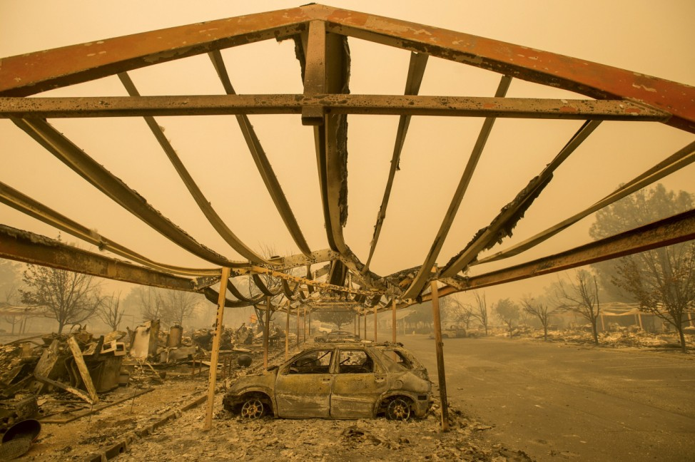 A destroyed vehicle rests under a carport after the Valley Fire raged through Middletown