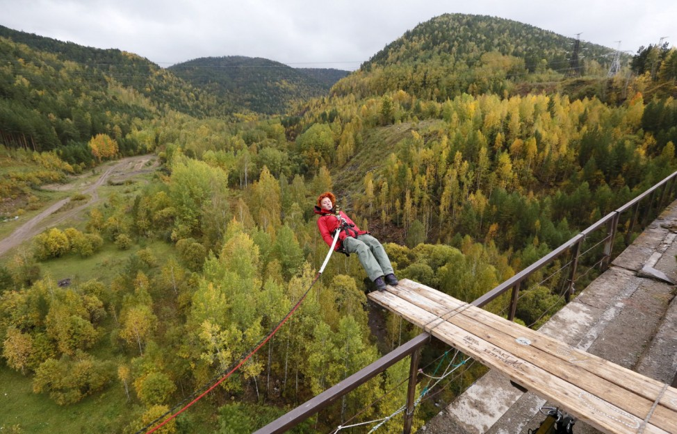 A member of the 'Exit Point' amateur rope-jumping group jumps from a 44-metre high waterpipe bridge in the Siberian Taiga area outside Krasnoyarsk