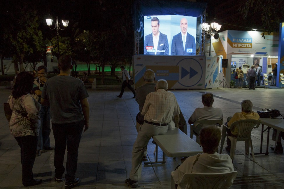 People watch a televised electoral debate in Syntagma square in Athens