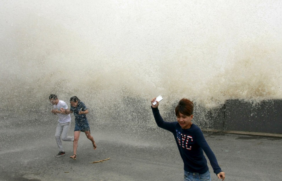 Visitors run away from a wave caused by a tidal bore which surged past a barrier on the banks of Qiantang River, in Hangzhou
