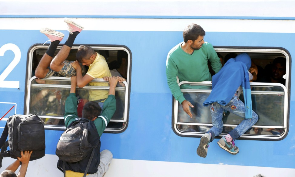 Migrants scramble through a train's window at the station in Beli Manastir