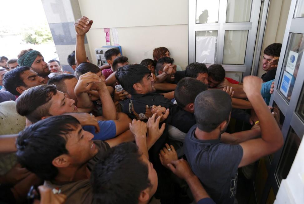 Migrants wrestle to buy train ticket at the train station in Beli Manastir