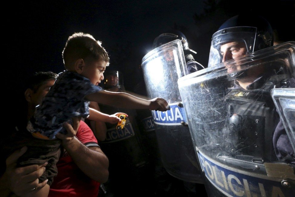 A migrant holds a child in front of Slovenian police at the boarder from Croatia to Slovenia in Harmica
