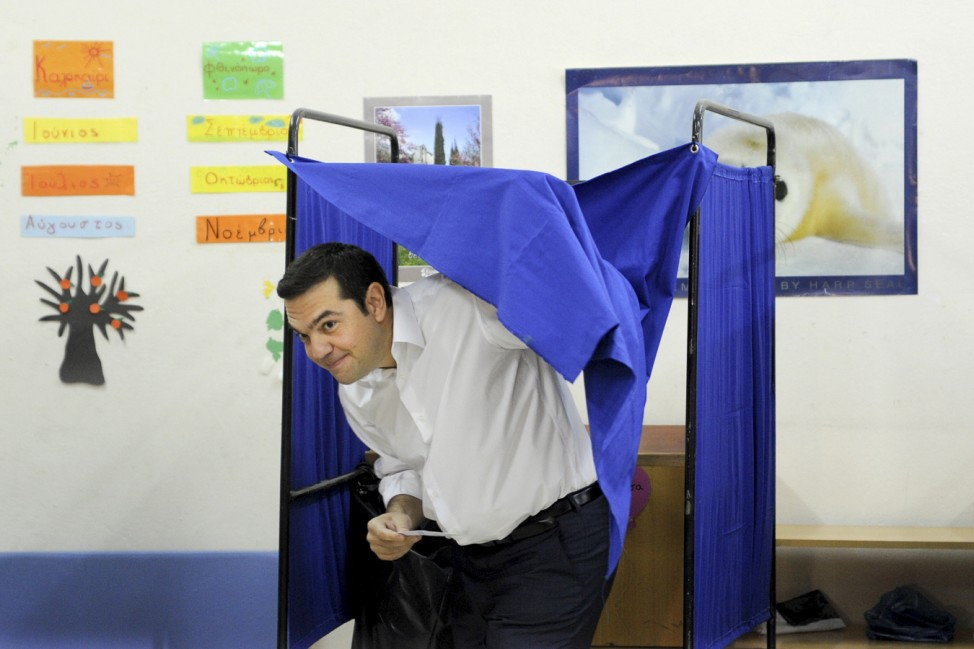 Former Greek prime minister and leader of leftist Syriza party Tsipras holds his ballot as he exits a voting booth during the general election at a polling station in Athens