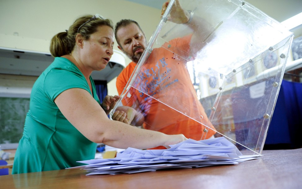 Election workers empty a ballot box at a polling station after polls closed in a general election in Athens