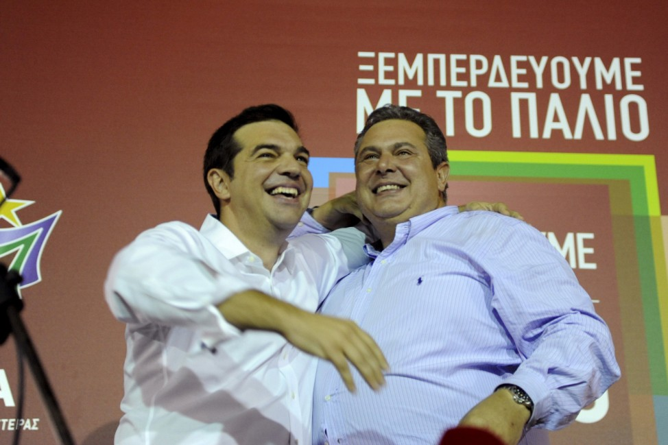 Former Greek prime minister and leader of leftist Syriza party Alexis Tsipras hugs coalition partner and leader of the Independent Greeks party, Panos Kammenos after winning the general election in Athens