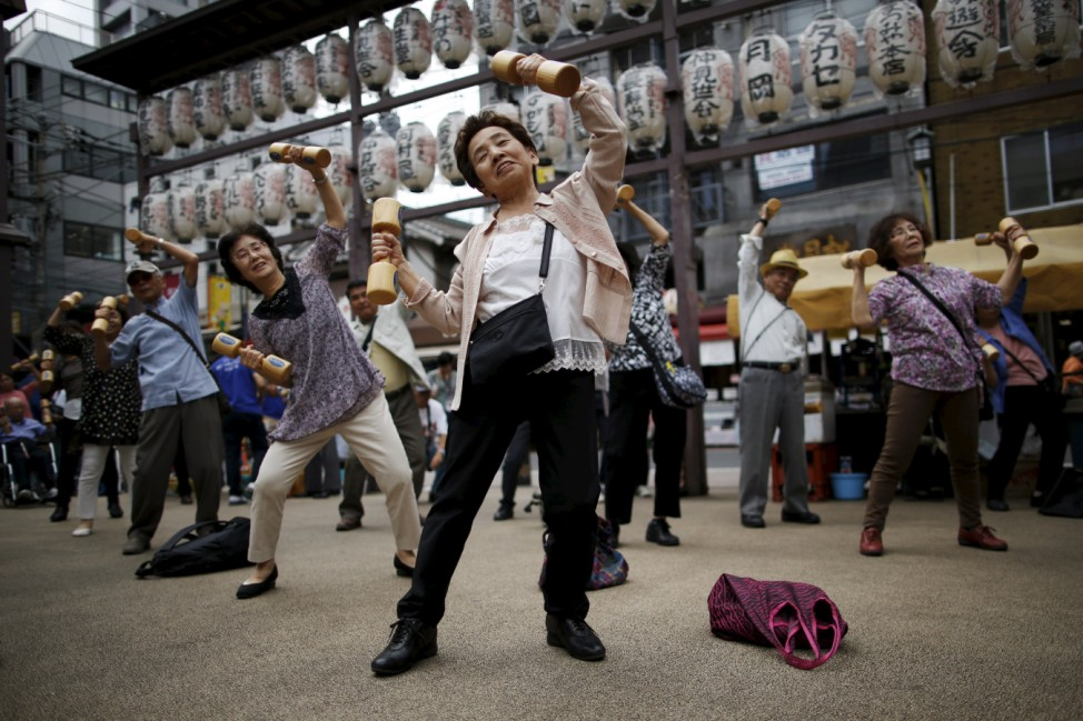 Elderly and middle-age people exercise with wooden dumbbells during a health promotion event to mark Japan's 'Respect for the Aged Day' at a temple in Tokyo