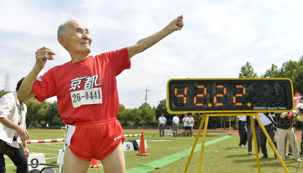 Japanese Hidekichi Miyazaki poses like Jamaica's Usain Bolt in front of an electric board showing his 100-metre record time of 42.22 seconds at an athletic field in Kyoto