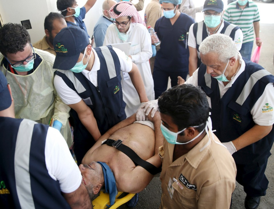 Medical staff carry a way wounded pilgrim following a crush caused by large numbers of people pushing at Mina, outside the Muslim holy city of Mecca