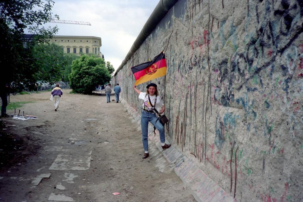 Touristin an der Berliner Mauer (Niederkirchner Straße) mit DDR - Flagge 1990