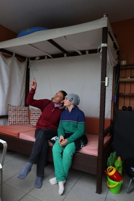 """München: Fabian und seine Mama sitzen Probe auf einem Balkon von """"Lindenhof""""."""