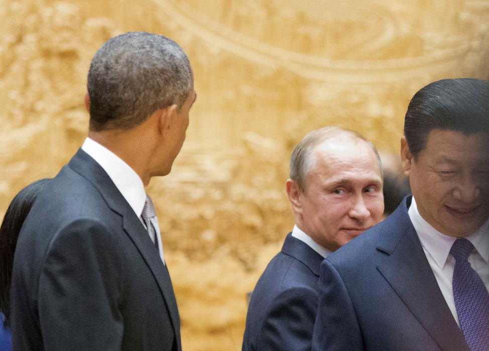 Putin looks back at Obama as they arrive with Xi Jinping at APEC Summit plenary session in Beijing