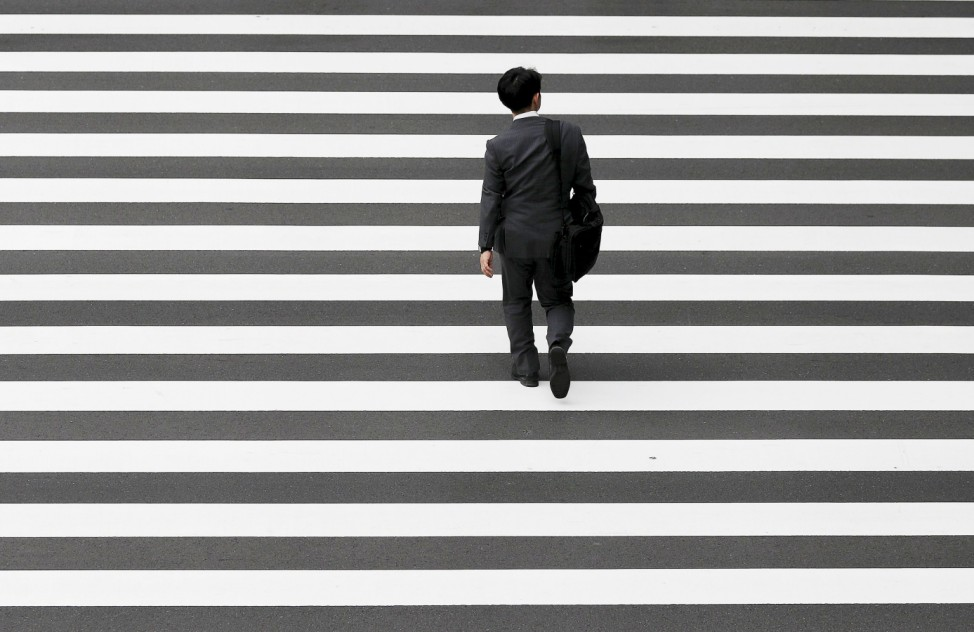 A businessman crosses a road at Tokyo's business district
