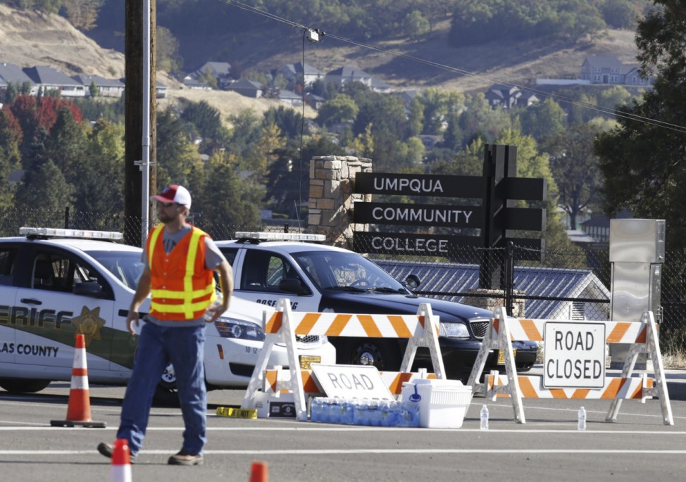 Police cruisers block the entrance to the site of a mass shooting at Umpqua Community College in Roseburg