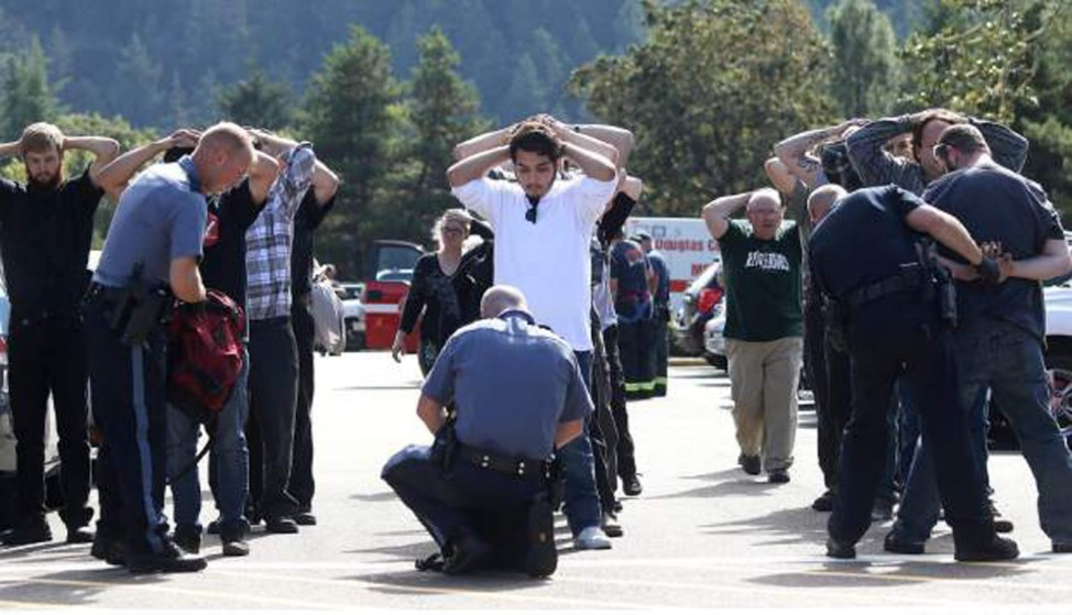 Police officers inspect bags as students and staff are evacuated from campus following a shooting incident at Umpqua Community College in Roseburg Oregon