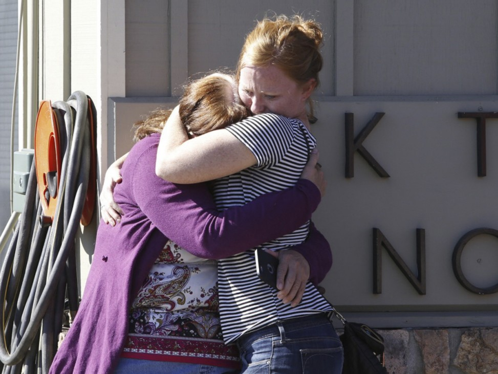 College alumnus is embraced after a mass shooting at Umpqua Community College in Roseburg