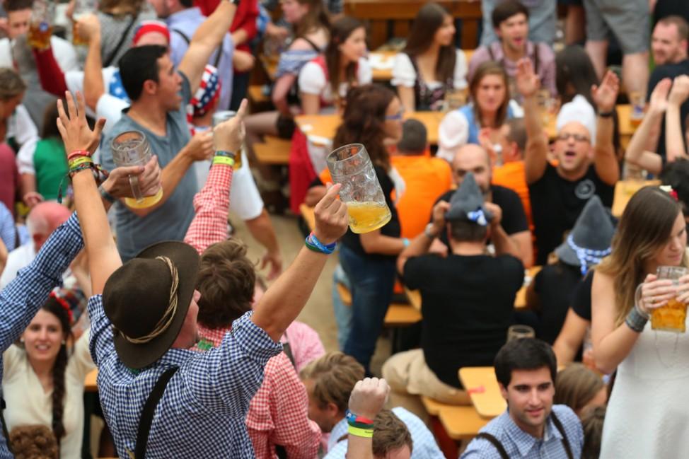Oktoberfest-Besucher mit Masskrug in der Hand im Bierzelt in München